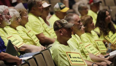 "People with ""I am the evidence"" signs listen to experts giving presentations at a Brown County meeting regarding health effects of wind turbines at the Bay Port High School Performing Arts Center on Tuesday, September 12, 2017 in Suamico, Wis."