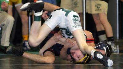 New Providence High School's Owen Smith (white and green singlet) wrestles last season.