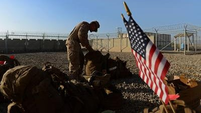 A US Marine arranges his equipment as British and US troops withdraw from the Camp Bastion-Leatherneck complex at Lashkar Gah in Helmand province on October 26, 2014.