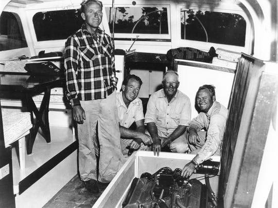 Captains Johnson Whiticar (left), Curt Whiticar (kneeling), Addison Whiticar and Jack Whiticar (right), all of Stuart, work on a boat's motor in this 1950s era photo.