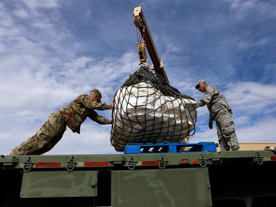 Sgt. James Ray, left, and Staff Sgt. Noe Amador with the New Mexico Army National Guard's 1116th Transportation Company on Oct. 29 secure the remains of a Pentaceratops to a flatbed trailer in the Bisti/De-Na-Zin Wilderness south of Farmington.