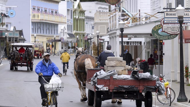 A dray horse pulls a wagon loaded with stones down Main Street on Mackinac Island.