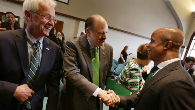 James M. Smith, center shakes hands with basketball coach Rob Murphy as vice president for communication Walter Kraft, left looks on after being elected as the 23rd president of Eastern Michigan University by the Board of Regents at Eastern Michigan University in Ypsilanti on Friday, February 12, 2016.