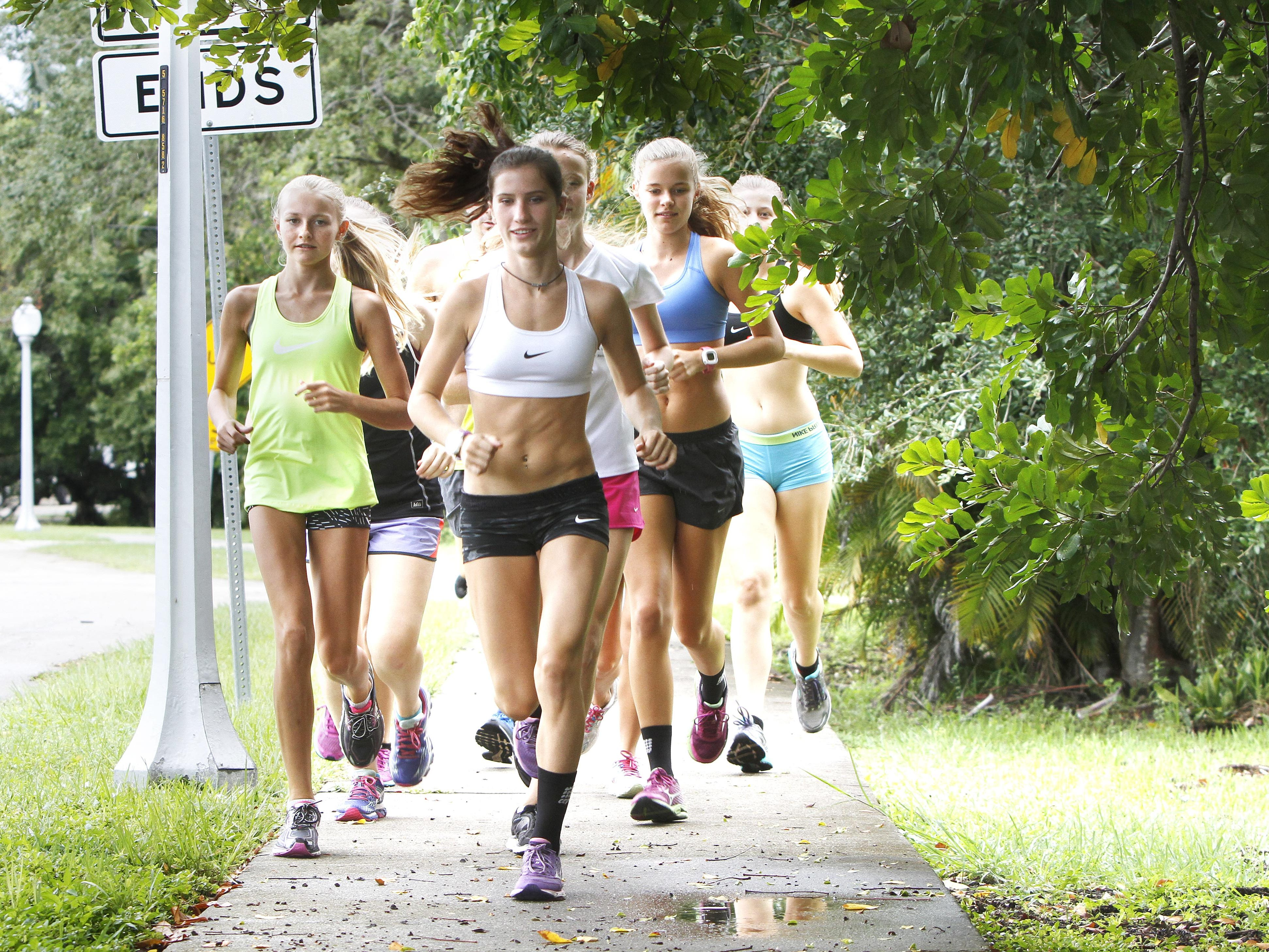 The Fort Myers High School cross country team, led by junior Kristlin Gear, center, runs the neighborhood sidewalks of historic Fort Myers Friday, August 28.