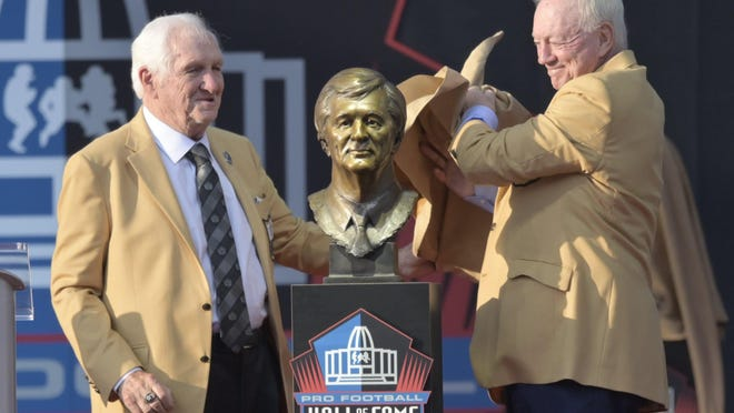 Former NFL football executive Gil Brandt, left, and presenter Jerry Jones, owner of the Dallas Cowboys, unveil the bust of Brandt during the induction ceremony at the Pro Football Hall of Fame, Saturday, Aug. 3, 2019, in Canton, Ohio.