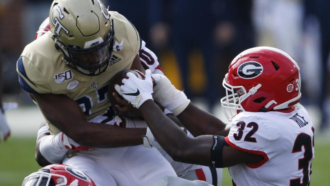 Georgia inside linebacker Monty Rice (32) tries to strip the ball from Georgia Tech punter Pressley Harvin III (27) during the game Nov. 30, 2019, in Atlanta.