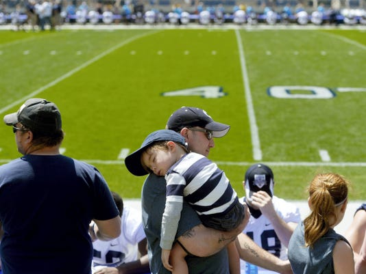 Carter Menuchak, 3 of Schuylkill County, sleeps on his father Rich's shoulder during Saturday's autograph session at Beaver Stadium.