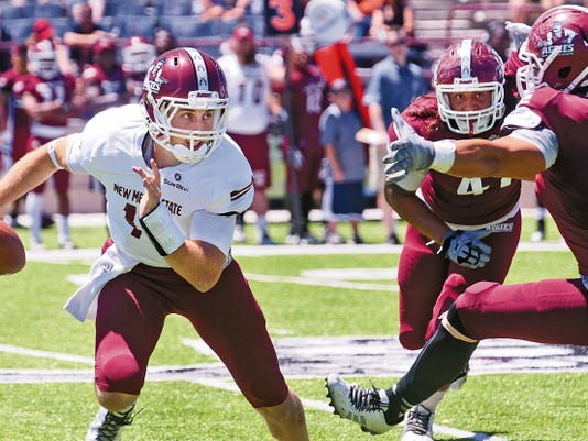 Gary Mook/For the Las Cruces Sun-News   New Mexico State quarterback Tyler Rogers scrambles just out of reach of defensive lineman Stephen Meredith during the Aggie Spring Game Saturday afternoon at Aggie Memorial Stadium.