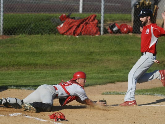 Dover's Chris Bubb scores as Manchester catcher Chris Robinson dives for the ball during a Central League baseball game in Dover on July 16. Dover beat Manchester, 9-2.