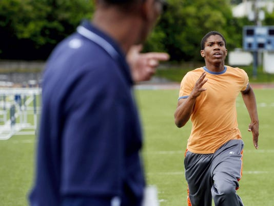 William Penn head track and field coach Tony Jones, left, urges on senior Larell Anderson during track and field practice at Small Field on Wednesday. Anderson will compete in the District 3 track and field championships in Shippensburg on Friday and Saturday, while also performing in 'Aida' at the Strand Capitol each night.