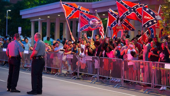 People wave Confederate flags outside the hotel where