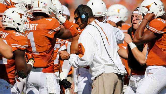Jay Norvell huddles with players when he was a coach at Texas in 2015. Norvell has agreed to become Nevada's head coach.