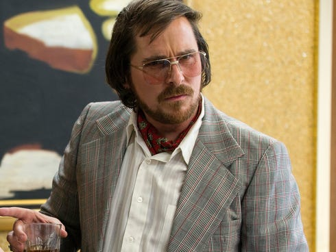 Irving Rosenfeld (Christian Bale) attempts to scam an under cover agent in a scene from the motion picture
