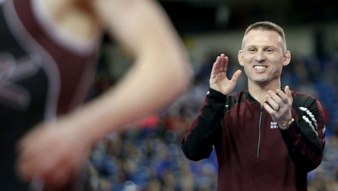 South Kitsap coach Chad Nass applauds Xavier Eaglin's win over Mead's Chase Randall during the Mat Classic Championships at the Tacoma Dome in February 2018.