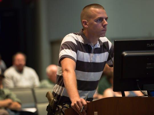 Law enforcement officer Riley Mayer speaks against