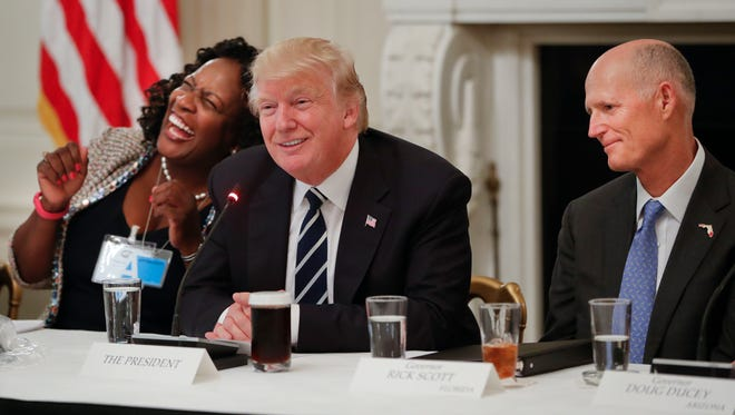President Trump smiles as he sits with  Fontana (Calif.) Mayor Acquanetta Warren, and Florida Gov. Rick Scott during his meeting with mayors and governors for a Infrastructure Summit in the State Dinning Room of the White House Thursday.