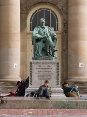 Cornell University students study beside a statue of
