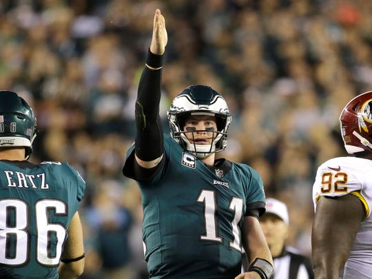 FILE - In this Monday, Oct. 23, 2017, file photo, Philadelphia Eagles quarterback Carson Wentz (11) gestures after scrambling for yardage against the Washington Redskins during the second half of an NFL football game in Philadelphia. Wentz and the Philadelphia Eagles are the talk of the NFL following a surprising 8-1 start.