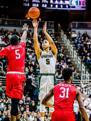 Bryn Forbes, center, of MSU knocks down a 3-point shot over Mike Williams, left, of Rutgers during the 1st half of their game Sunday.