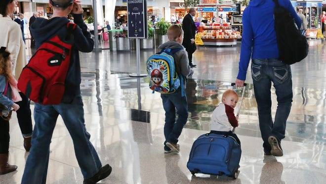 At Indianapolis International Airport, a young flier caught a ride on a suitcase Monday, Oct. 19, 2015 as a group of airline passengers headed into Civic Plaza and a Transportation Security Administration checkpoint.