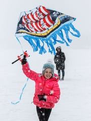 """Gianna Shields, 7, of Pewaukee, tries to launch her kite during the annual """"Fly a Kite on Ice"""" event hosted by Silly Willyz toy store in Pewaukee on Saturday, Feb. 3, 2018."""