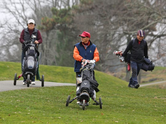 Nam Whang, left, Joon Yew, and Young Shin golf at Saxon Woods golf course in Scarsdale Dec. 9, 2015. The three New Jersey residents were golfing with a friend from Hastings-on-Hudson. Mild temperatures are allowing golfers to extend the golf season late into the fall.