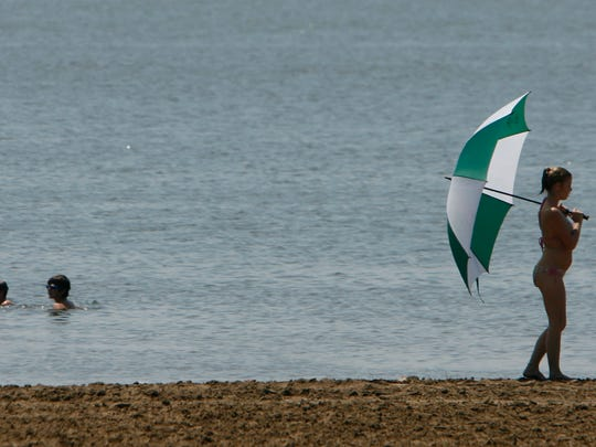 A woman walks with an umbrella along the beach at Big Creek in this file photo from 2014.