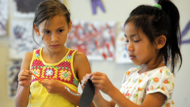 Cassidy Bruton, 8, left, and Lauren Korsgaden, 6, create and decorate a butterfly Thursday during the Visalia Parks and Recreation's Creative Minds Art Camp in the Rawhide Room at Recreation Park, Rawhide baseball stadium, 400 N. Giddings St.
