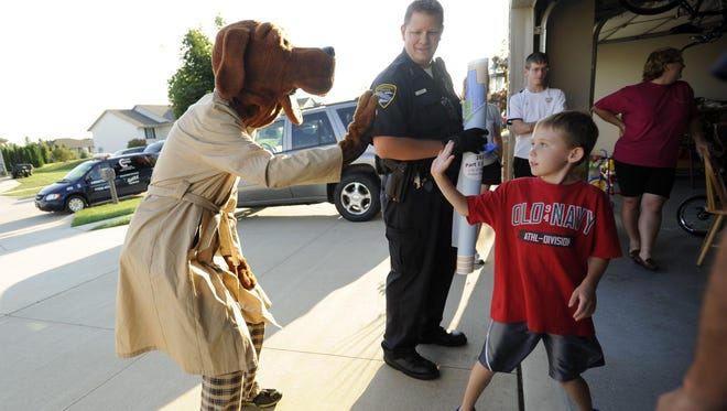Officer Richard Ladwig, back, watches as Andrew Ballard of Manitowoc, 8, gives a high-five to McGruff the Crime Dog in 2012.