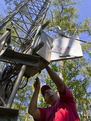 Barclay Shoemaker, a research hydrologist for the U.S. Geological Survey, works on a repair at one of the USGS weather monitoring towers at Big Cypress National Preserve off Loop Road.