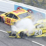 Joey Logano (22) and Matt Kenseth (20) tangle in tun one during the Sprint Cup auto race at the Martinsville Speedway in Martinsville, Va., Sunday, Nov. 1, 2015.    (AP Photo/Don Petersen)