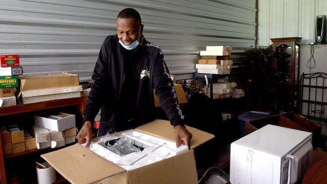 Larry McBride opens a box containing a new toaster oven that someone set out on the curb when area college students were moving. McBride collects used furniture and other items that people discard and uses proceeds from sales to retire his child support debt.