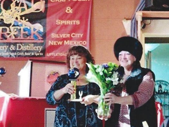 Cheryl Howell of Las Cruces, at left, accepts a bouquet