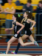 Padua's Lydia Olivere (left) and Tatnall's Keelin Hays run in stride before Hays won the 1600 meter race during the DIAA state indoor track championships Saturday in Landover, Md.