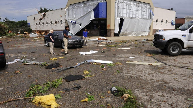 People pick up debris near the damaged Rite Aid store in Portland after severe storms Monday, A tornado watch is in effect until 3 a.m. Tuesday.
