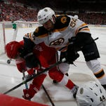 Detroit Red Wings' Justin Abdelkader takes an elbow from Boston Bruins' Adam McQuaid behind the Bruins goal in the second period on Thursday, April 2, 2015 in Detroit.
