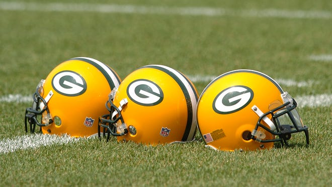 Helmets sit on the practice field during Green Bay Packers organized team activities at Clarke Hinkle Field.