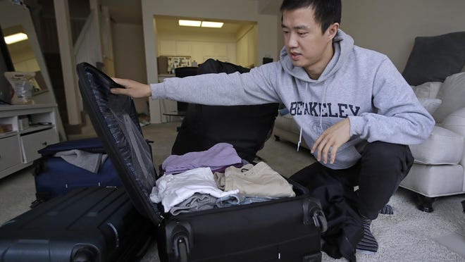 "In this Monday, Feb. 4, 2019, photo, Leo Wang packs a suitcase at his home in San Jose, Calif. Wang has found himself trapped in an obstacle course regarding H-1B work visas for foreigners. His visa denied and his days in the United States numbered, Wang is looking for work outside the country. ""I still believe in the American dream,"" he says. ""It's just that I personally have to pursue it somewhere else."""