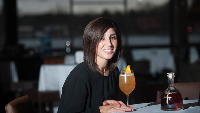 Heather Neborak shows a popular Apricot 75 drink made with Cognac at the ChopHouse in Gibbstown.