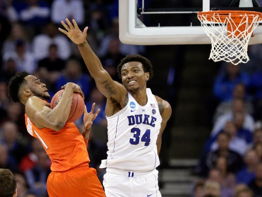 Syracuse's Oshae Brissett, left, holds the ball as Duke's Wendell Carter Jr (34) defends during the second half of a regional semifinal game in the NCAA men's college basketball tournament Friday, March 23, 2018, in Omaha, Neb. (AP Photo/Nati Harnik)