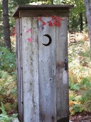 A typical outhouse in Wisconsin, sporting a crescent-moon decoration on the door.