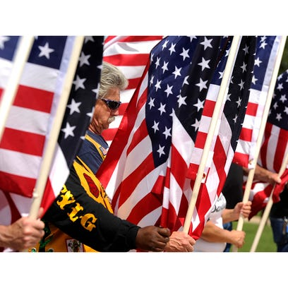 Mark Baidas holds a flag during the Memorial Day ceremony