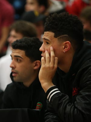 Suns Devin Booker watches the Chino Hills vs. Shadow Mountain during the Hoophall West tournament at Chaparral High School on December 8, 2017 in Phoenix, Ariz.