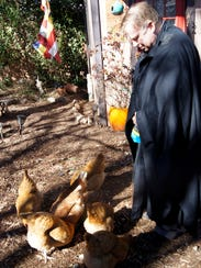 Zen Priest Dr. Paul Stuetzer feeds his chickens after
