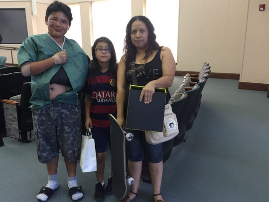 Gabriel Ozuna, 13, with his sister and mother on May 18, a day after he was hit by a car while skateboarding.