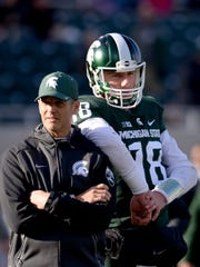 Brad Salem, here with Connor Cook in 2015, moves from Michigan State's quarterbacks coach to offensive coordinator and running backs coach this fall.