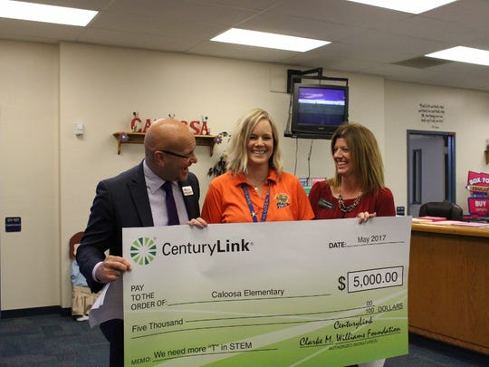 Caloosa Elementary School STEM (Science, Technology, Engineering and Mathematics) teacher Kimberly Jordan, shown center, accepts a check from Marshall Bower and Shelly Chitwood.
