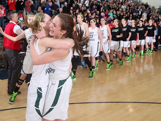 Brielle Carleen of New Providence, left hugs teammate