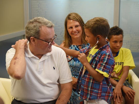Exavier Giles, 6, the youngest of Giles' three sons, listens with a stethoscope to the breathing of Callahan, as his mother, Dr. Eran Muto-Giles, observes.