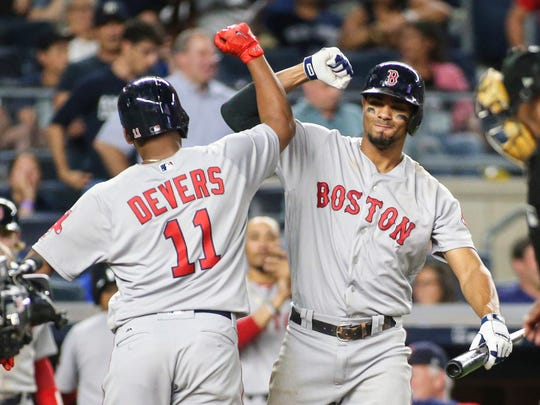 Boston Red Sox designated hitter Rafael Devers (11) is congratulated by shortstop Xander Bogaerts (2) after hitting a solo home run in the ninth inning against the New York Yankees at Yankee Stadium.